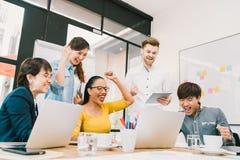 Den multietniska olika gruppen av coworkers firar samman med bärbara datorn och minnestavlan Idérikt lag eller tillfällig affärsk Arkivfoto