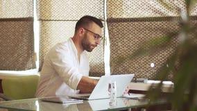 Den Multitasking affärsmannen på arbete, skriver en penna i en anteckningsbok, bärbar dator, gör anmärkningar i minnestavlan lager videofilmer