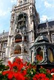 Den Munich Rathaus-Glockenspielen som lokaliseras på Marienplatzen på en sommareftermiddag Arkivfoton