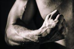 Den muskulösa armen av en säker ung man - en kroppsbyggareidrottsman nen som gripas hårt om in i en näve begreppet av styrka, övn arkivbild