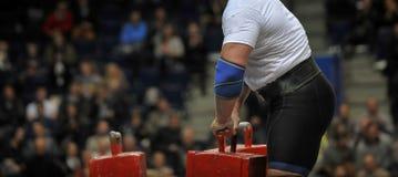Den muskulösa idrottsmannen som gör bonden, går övning under hans konkurrensgenomkörare Strongmansport royaltyfria foton