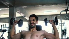 Den muskulösa kraftiga unga mannen som gör skuldror trycker på uppe i luften, att lyfta med hantlar i konditionidrottshall lager videofilmer