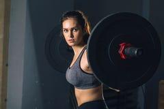 Den muskulösa kvinnan i en idrottshall som gör tungvikten, övar med skivstången Arkivfoto