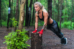 Den muskulösa kvinnan som gör push-UPS på, parkerar gatan utarbetar royaltyfria bilder