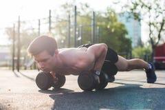 Den muskulösa manliga idrottsman nen som att göra skjuter, ups övningar arkivfoton