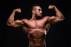 Den muskulösa mannen för konditionburnetskägget visar biceps på svart bakgrund royaltyfria foton