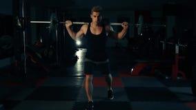 Den muskulösa mannen i idrottshallen som utbildar hans ben quadriceps och knäsena med en stång, byter begrepp av kondition och bo arkivfilmer