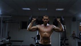 Den muskulösa mannen i idrottshallutbildningen med hantlar, grabb pumpar hans deltaformade muskel lager videofilmer