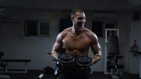 Den muskulösa mannen i idrottshallutbildningen med hantlar, grabb pumpar hans deltaformade muskel arkivfilmer