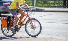 Den muskulösa mannen i t-skjorta och kortslutningar föredrar en aktiv livsstil, och ritter cyklar arkivfoto