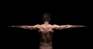 Den muskulösa mannen med armar sträckte ut på svart bakgrund Arkivbild