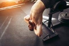 Den muskulösa mannen som övar att göra, sitter upp övning Arkivfoton