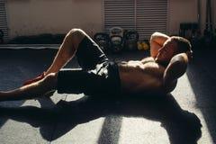 Den muskulösa mannen som övar att göra, sitter upp övning Royaltyfri Foto