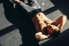 Den muskulösa mannen som övar att göra, sitter upp övning Fotografering för Bildbyråer