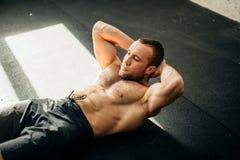 Den muskulösa mannen som övar att göra, sitter upp övning Arkivfoto