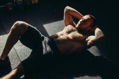Den muskulösa mannen som övar att göra, sitter upp övning Royaltyfri Fotografi
