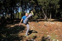 Den muskulösa mannen som gör genomkörare, värmer upp av det stigande benet upp i luftövningen i skog Royaltyfria Bilder