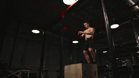 Den muskulösa mannen utan en skjorta utför vertikala hopp på en träask aerobisk övning stock video