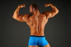 Den muskulösa mannen visar hans baksida Arkivfoto