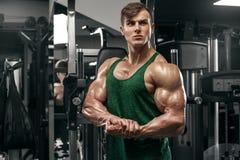 Den muskulösa manvisningen tränga sig in att utarbeta i idrottshallen, stark man med stor biceps royaltyfri fotografi