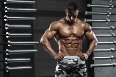 Den muskulösa manvisningen tränga sig in och att posera i idrottshall Stark manlig naken torsoabs som utarbetar royaltyfri bild