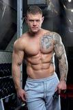 Den muskulösa shirtless strimlade starka avkopplade mannen med blåa ögon och tatueringen poserar i flåsanden för en grå färg i en Royaltyfri Foto