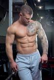 Den muskulösa shirtless strimlade starka mannen med blåa ögon och tatueringen poserar i flåsanden för en grå färg i en idrottshal Royaltyfria Bilder