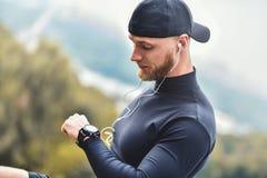 Den muskulösa skäggiga idrottsman nen som kontrollerar brända kalorier på den smarta klockan efter bra genomkörareperiod på stad, arkivfoton