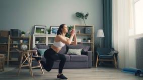 Den muskulösa unga kvinnan gör squats som koncentreras inomhus på fysisk övning lager videofilmer
