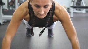 Den muskulösa unga kvinnan som att göra skjuter, ups i idrottshallen Idrotts- flicka som inomhus övar Sund livsstil för genomköra arkivfilmer