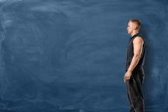 Den muskulösa unga mannen är stå och se framåtriktat på blå svart tavlabakgrund arkivbild