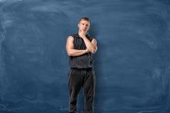 Den muskulösa unga mannen är stå och tänka rymma hans huvud med handen på blå svart tavlabakgrund royaltyfri foto