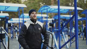 Den muskulösa unga mannen som gör övning i utomhus- idrottshall i vinter, parkerar stock video