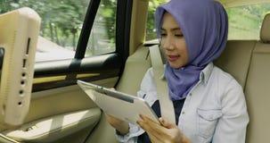 Den muslimska kvinnan använder minnestavlan i bilen lager videofilmer