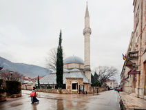 Den muslimska kvinnan går förbi moskén arkivfoton