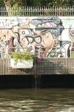 Den muslimska kvinnan går vid en grafitti vid en kanal i Bangkok, Thailand arkivbild