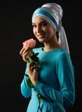 Den muslimska kvinnan i blått klär med rosblomman Arkivbild