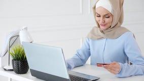 Den muslimska kvinnan i hijab k?per direktanslutet med en kreditkort och en b?rbar dator arkivfilmer