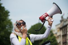 Den muslimska kvinnan med megafonen på räknare-demonstrationen av tryckgruppen förenar mot fascism i Whitehall, London, UK Arkivbilder