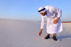Den muslimska mannen framkallar sand längs vind och anseende i mitt av de Royaltyfria Bilder