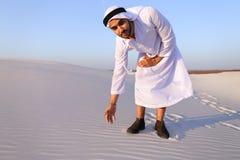 Den muslimska mannen framkallar sand längs vind och anseende i mitt av de Arkivbild