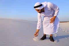Den muslimska mannen framkallar sand längs vind och anseende i mitt av de Arkivfoton