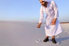 Den muslimska mannen framkallar sand längs vind och anseende i mitt av de Royaltyfri Fotografi