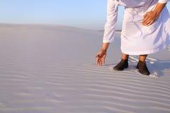 Den muslimska mannen framkallar sand längs vind och anseende i mitt av de Royaltyfri Foto
