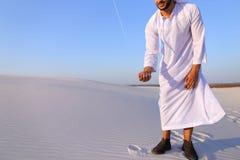 Den muslimska mannen framkallar sand längs vind som står i mitt av öknen Arkivfoto