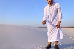 Den muslimska mannen framkallar sand längs vind som står i mitt av deser Arkivfoto