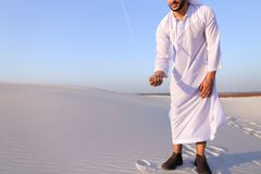 Den muslimska mannen framkallar sand längs vind som står i mitt av deser Royaltyfri Foto