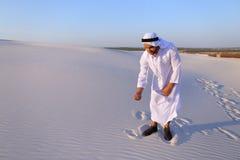 Den muslimska mannen framkallar sand längs vindanseende i mitt av öknen Royaltyfri Bild