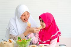 Den muslimska modern och hennes dotter äter kakor samman med en bunke av grönsaksallad på vit bakgrund royaltyfria bilder
