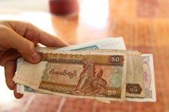 Den Myanmar sedelkyaten vecklas upp i hand Arkivfoto